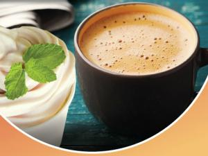 A cup of cocoa froyo with a mint leaf garnish next to a warm mug of cocoa.