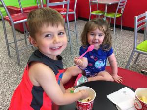 two children in summer clothes eating frozen yogurt on a sunny day