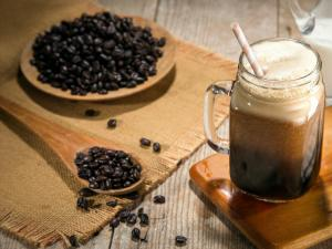coffee beans and a cup of cold brew on a wooden counter top