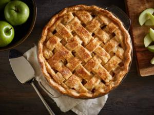 apple pie on a dark wood surface with apples